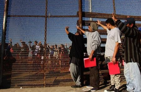 Recently deported immigrants gathered at the border between San Diego and Tijuana in 2011.