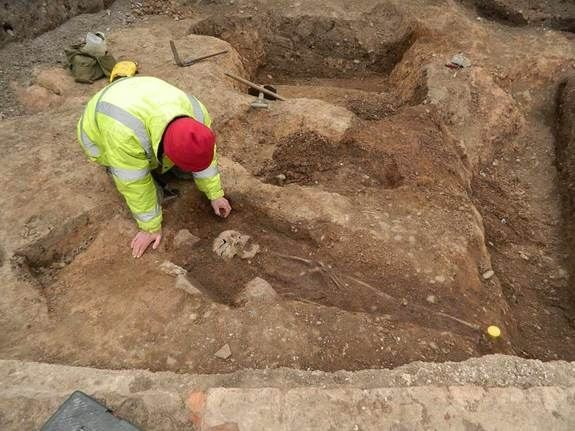 Archaeologist excavating burials in Leicester, England parking lot