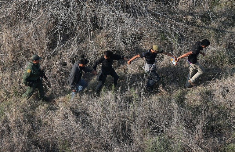 A Border Patrol agent escorts a group of undocumented immigrants in the Rio Grande Valley.