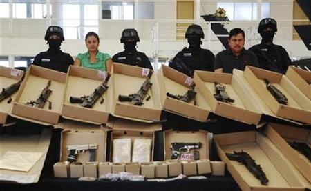 Mexican police display confiscated weapons and two arrested Zeta members in 2010.
