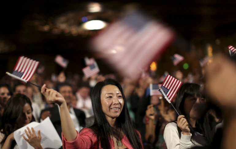 A woman waves a flag during a U.S. Citizenship and Immigration Services naturalization ceremony in Oakland.