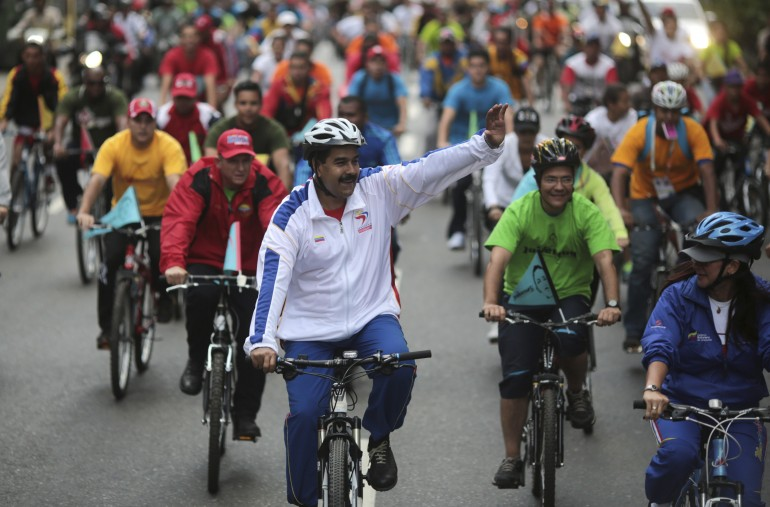 Maduro waves to the crowd as he and his fellow riders take a spin around the center of Caracas.