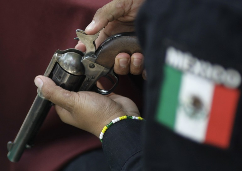 A Mexico City police officer checks a gun handed in as part of a voluntary disarmament program.