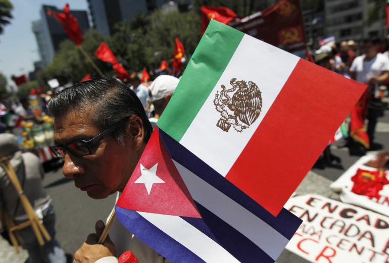 A man holds up a Cuban and Mexican flag in Mexico City in July during an event marking the 1953 Moncada military barracks assault in Cuba.