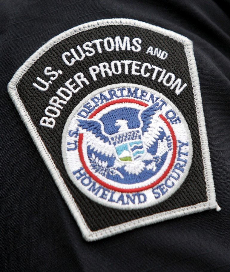 A US Customs and Border Protection badge.