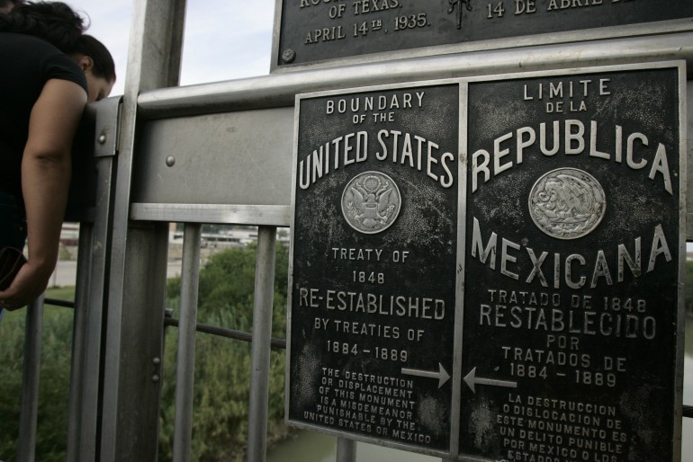 A sign on a cross-border bridge marking the border between the US and Mexico.