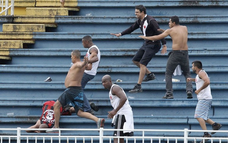 as they help an Atletico Paranaense fan during clashes between Vasco da Gama soccer fans and Atletico Paranaense fans at their Brazilian championship match in Joinville in Santa Catarina state
