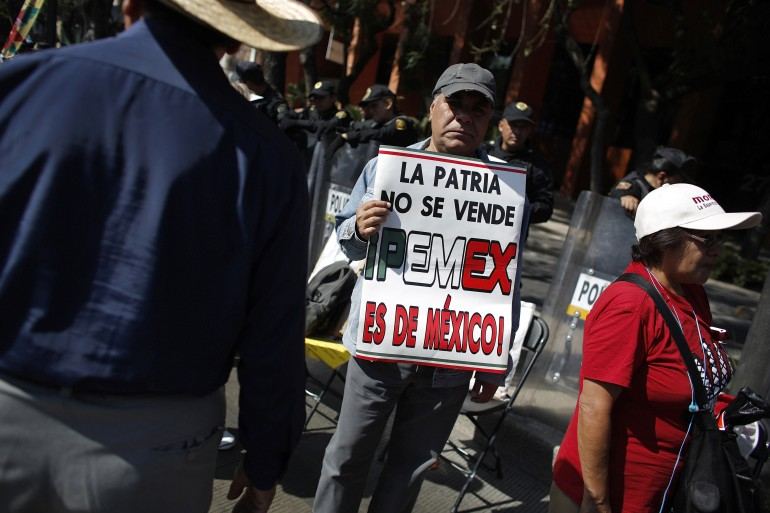 A demonstrator holds a placard that reads 'Homeland is not for sale, Pemex is for Mexico' during a protest against the energy reform bill outside the Senate building in Mexico City December 6, 2013.