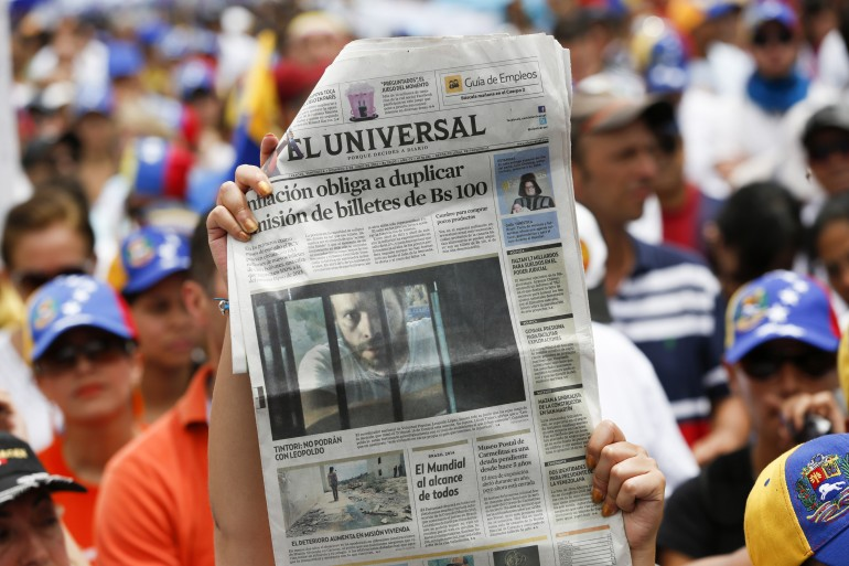Opposition supporters hold up El Nacional.