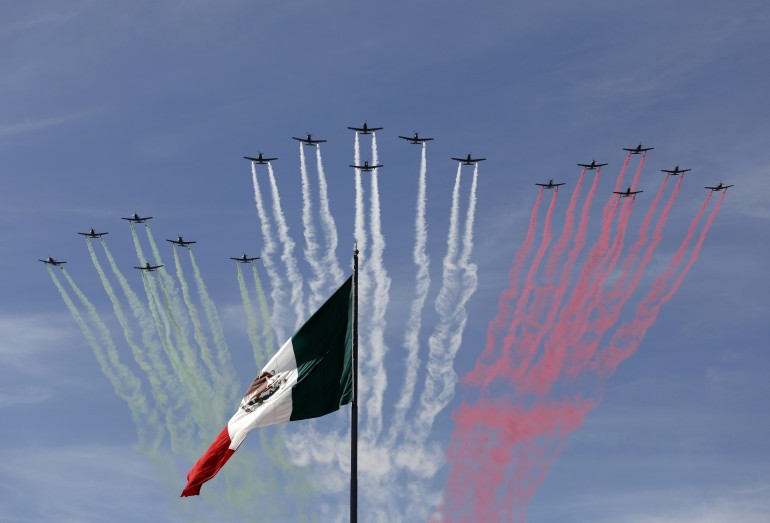Planes fly in formation over the Mexican national flag