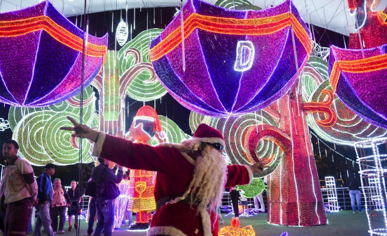 a man dressed as santa claus gestures next to the christmas lights on december 9 2014 in medellin antioquia department colombia afp photoraul arboleda