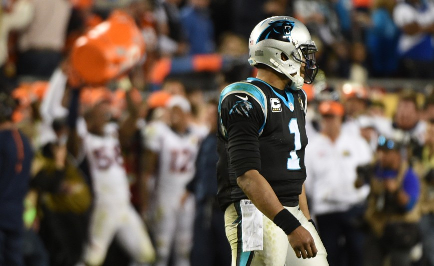 Cam Newton Walks off the Field as Broncos Celebrate in Background