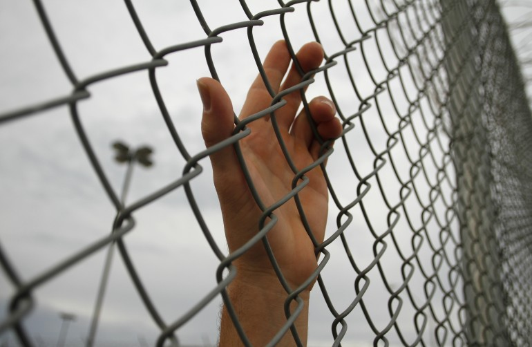 hand behind chainlink fence