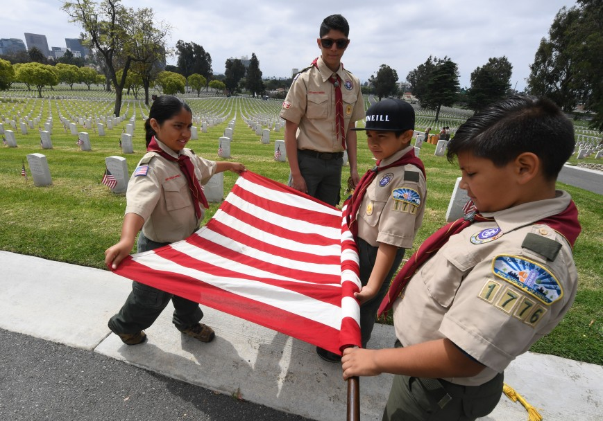Boy Scouts from the Long Beach troop prepare a US flag besides the graves of war veterans during the annual 'Flag Placement ceremony' to honor the fallen for Memorial Day at the Los Angeles National Cemetery, California