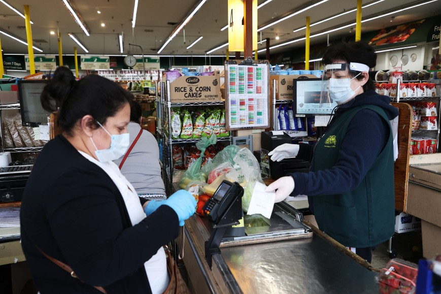 A shopper and cashier both wear masks, gloves and the cashier also has on a plastic visor at the checkout station Pat's Farms grocery store