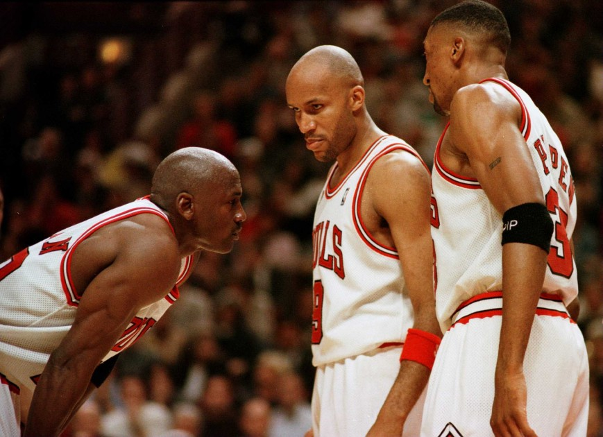 Michael Jordan of the Chicago Bull, left, discusses strategy with teammates Ron Harper, center, and Scottie Pippen during a time-out on the court during the fourth quarter of game two in the NBA Finals at the United Center