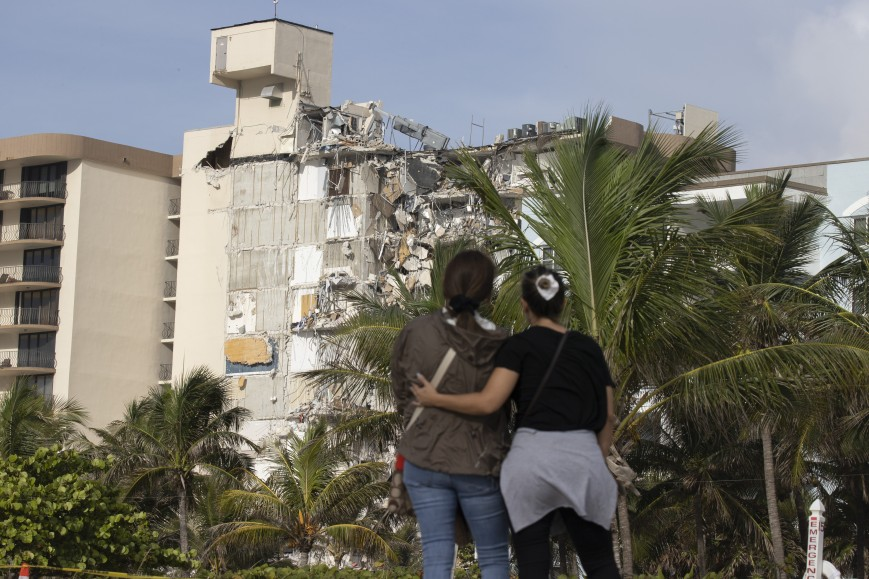 Maria Fernanda Martinez and Mariana Cordeiro (L-R) look on as search and rescue operations continue at the site of the partially collapsed 12-story Champlain Towers South condo building on June 25, 2021 in Surfside, Florida.