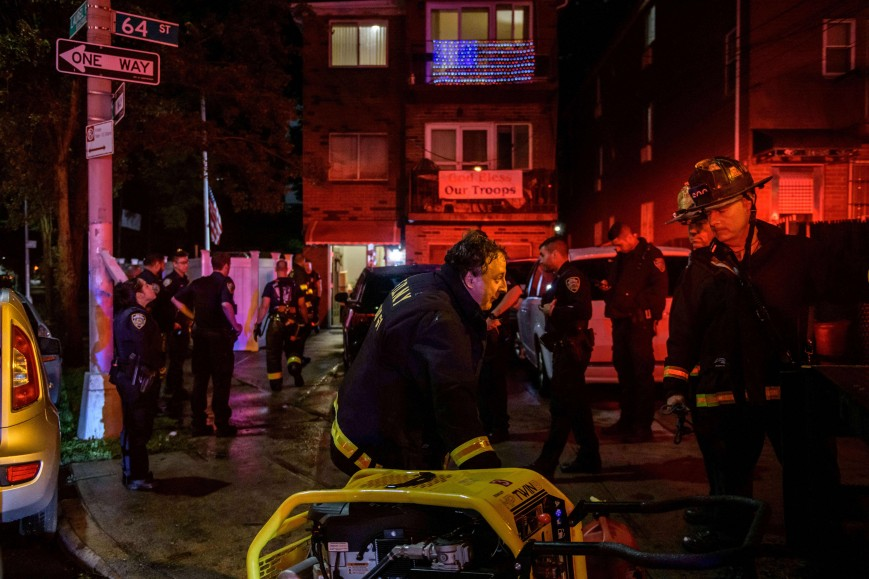 Police officers and rescue workers gather outside a house where a person was trapped in a flooded basement in Queens, New York