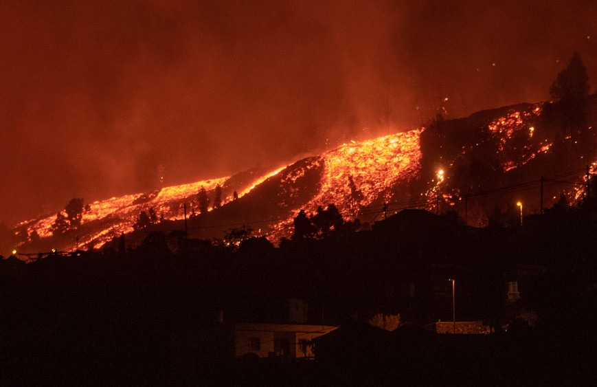 Lava flows approach houses as the Mount Cumbre Vieja erupts in El Paso, spewing out columns of smoke, ash and lava as seen from Los Llanos de Aridane on the Canary island of La Palma, on September 19, 2021.