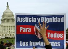 A woman holds up a sign during a protest rally for immigrants rights on Capitol Hill in Washington October 8, 2013.