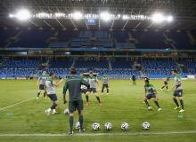 Australian soccer players warm up on the pitch