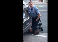 a-minneapolis-police-officer-holds-his-knee-to-AFP_1SE6IE