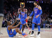 Chris Paul of the Oklahoma City Thunder is helped off the floor by Dennis Schroder and Steven Adams
