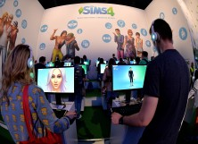 isitors try out the game 'SIMS 4' at the Electronic Arts stand at the 2014 Gamescom gaming trade fair