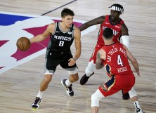 Bogdan Bogdanovic #8 of the Sacramento Kings drives against Jrue Holiday, back right, and JJ Redick #4 of the New Orleans Pelicans