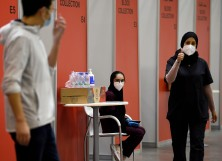 A nurse gives a thumbs up at Manama's repurposed convention centre, in which 6,000 people are participating in a large-scale trial of a Chinese-sponsored vaccine for the Covid-19 coronavirus, on August 27, 2020 in the Bahraini capital.