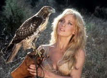 Tanya Roberts holding a perch with a bird on it in a scene from the film 'Sheena: Queen of the Jungle', 1984.