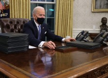 President Joe Biden prepares to sign a series of executive orders at the Resolute Desk in the Oval Office just hours after his inauguration