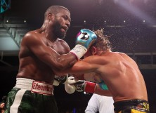 Floyd Mayweather exchanges blows with Logan Paul (yellow shorts) during their contracted exhibition boxing match at Hard Rock Stadium on June 06, 2021 in Miami Gardens, Florida.